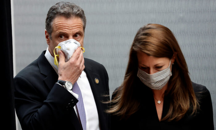 New York Gov. Andrew Cuomo holds a protective mask to his face as he and Secretary to the Governor Melissa DeRosa arrive for a briefing at New York Medical College in Valhalla, N.Y., on May 7, 2020. (Mike Segar/Reuters)