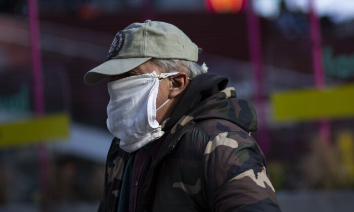 A man wears a double mask as he visits Times Square in New York on Dec. 10, 2020. (Kena Betancur/AFP via Getty Images)