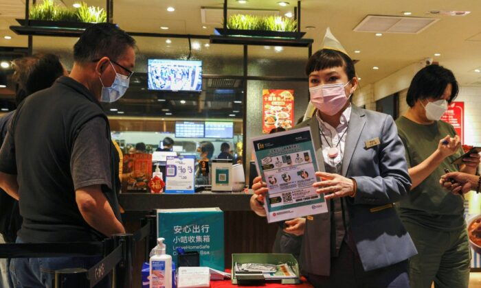 """A staff member holds an introduction of the """"LeaveHomeSafe"""" COVID-19 contact-tracing app at a restaurant, following the (COVID-19) outbreak, in Hong Kong, China, on Feb. 18, 2021. (Tyrone Siu/Reuters)"""