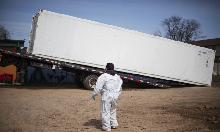 Gravedigger Thomas Cortez watches as a refrigerated trailer is delivered to keep pace with a surge of bodies arriving for burials, mostly those who died from COVID-19, at the Hebrew Free Burial Association's cemetery in the Staten Island borough of New York on April 7, 2020. (David Goldman/AP Photo)