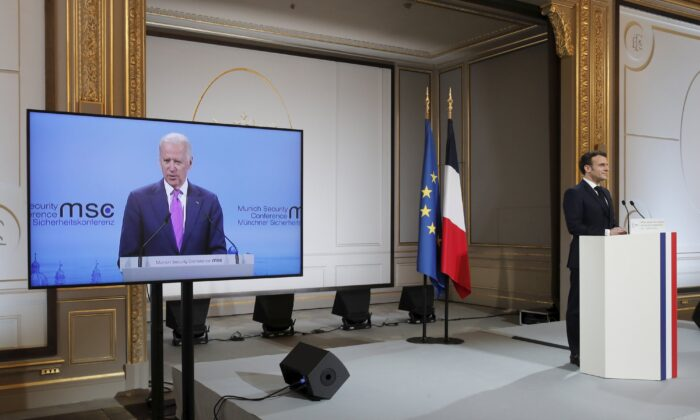 French President Emmanuel Macron, right, attends a video-conference meeting as U.S. President Joe Biden appear on a screen ahead of a 2021 Munich Security Conference at the Elysee palace in Paris on Feb. 19, 2021. (Benoit Tessier/Pool via AP)