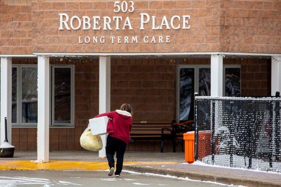 A woman carries items into Roberta Place, a long-term care facility which is the site of a COVID-19 outbreak, in Barrie, Ont., on Jan. 18, 2021.  (Carlos Osorio/Reuters)