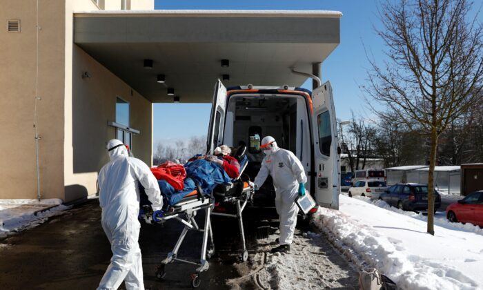 Medical workers move a COVID-19 patient into an ambulance at a hospital overrun by the pandemic in Cheb, Czech Republic on Feb. 12, 2021. (Petr David Josek/AP Photo/File)