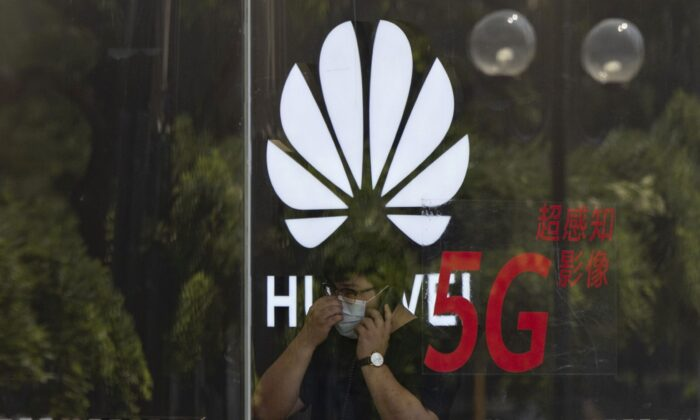 A worker talks on the phone in a Huawei store in Beijing on July 15, 2020. (AP Photo/Ng Han Guan, File)