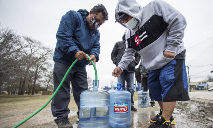 Victor Hernandez (L) and Luis Martinez fill their water containers with a hose from a spigot in Haden Park, in Houston, Texas, on Feb. 18, 2021. (Brett Coomer/Houston Chronicle via AP)