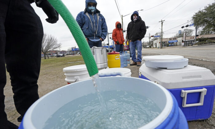 A water bucket is filled as others wait in near freezing temperatures to use a hose from public park spigot in Houston, Texas, on Feb. 18, 2021. (David J. Phillip/AP Photo)