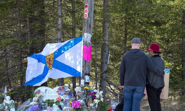 A couple pays their respects to the victims of the shooting at a makeshift memorial in Portapique, N.S., on April 22, 2020. (The Canadian Press)