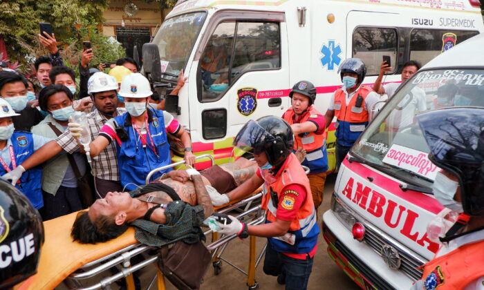 An injured man is carried by rescue workers after protests against the military coup, in Mandalay, Burma, on Feb. 20, 2021. (Stringer/Reuters)