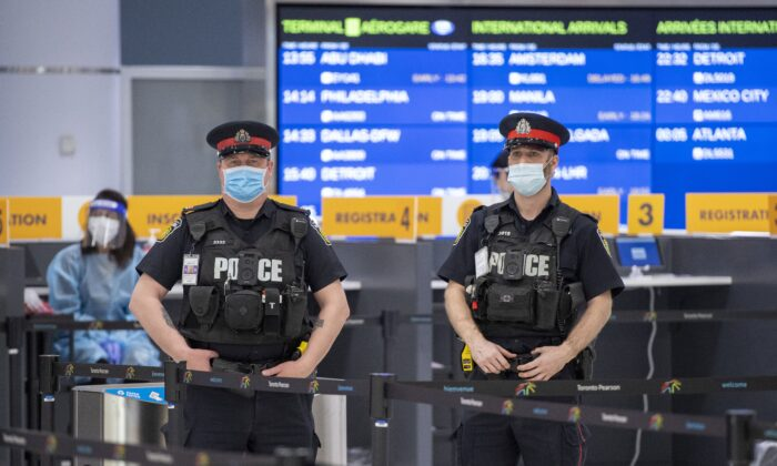 Police and health workers wait for arrivals at the COVID-19 testing centre in Terminal 3 at Pearson Airport in Toronto on Feb. 3, 2021. (The Canadian Press/Frank Gunn)