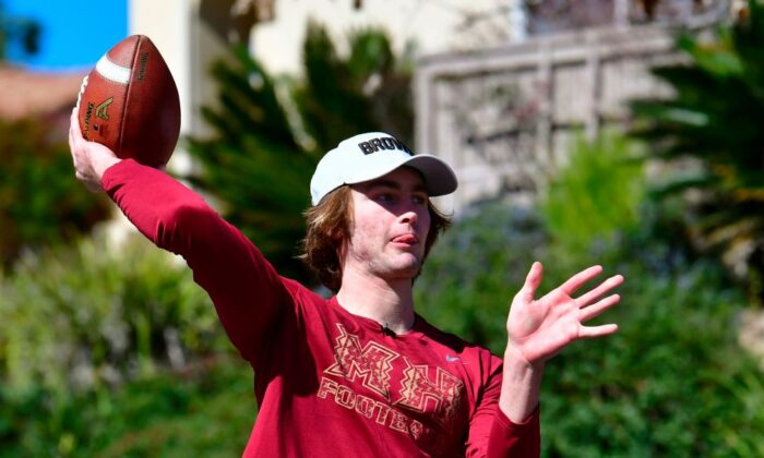High school football quarterback Gunnar Hensley throws to his dad Brad on neighborhood streets near their home in Carlsbad, Calif., on Feb. 18, 2021.(Frederic J. Brown/AFP)