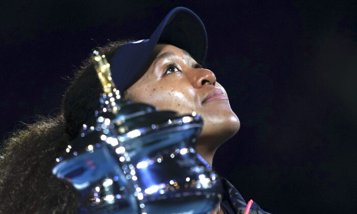Japan's Naomi Osaka holds the Daphne Akhurst Memorial Cup aloft defeating United States Jennifer Brady in the women's singles final at the Australian Open tennis championship in Melbourne, Australia, Saturday, Feb. 20, 2021.(Mark Dadswell/AP)