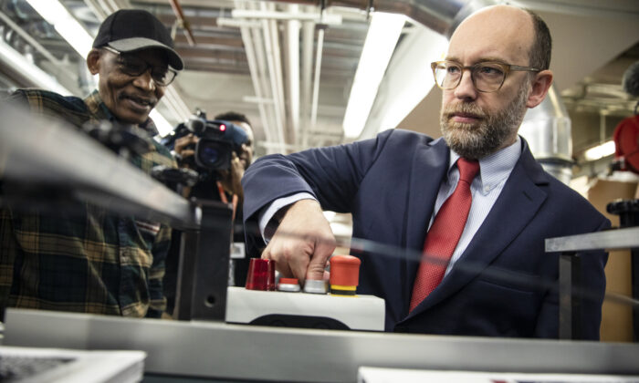 Acting Director of the Office of Management and Budget Russ Vought presses the button that starts the machine that will print copies of U.S. President Donald Trump's proposed budget for the U.S. Government for the 2021 Fiscal Year in Washington, on Feb. 6, 2020. (Samuel Corum/Getty Images)