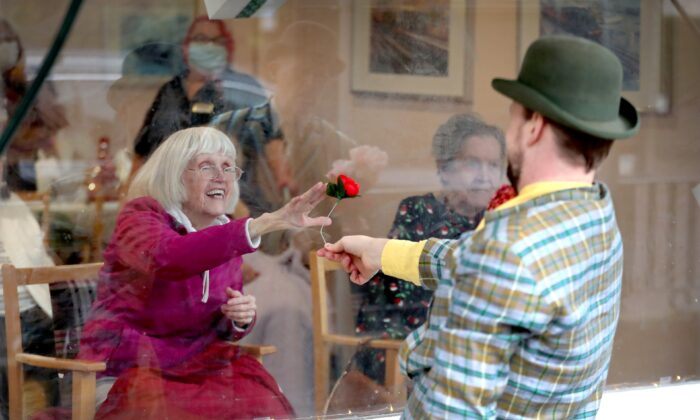 Award winning 'masters of the absurd' Dan Lees and Neil Frost of Mad Etiquette perform through the front window glass for residents at the Spring Lane Nursing Home in London, England, on Dec. 18, 2020. (Chris Jackson/Getty Images)