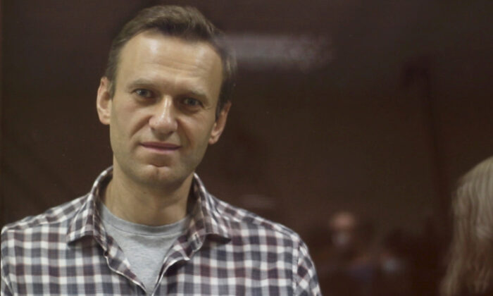 In this still image taken from video, Kremlin critic Alexei Navalny, who is accused of slandering a Russian World War II veteran, stands inside a defendant dock during a court hearing in Moscow on Feb. 20, 2021. (Press Service of Babushkinsky District Court of Moscow/Handout via Reuters)