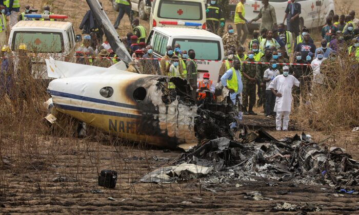 Rescuers and people gather near the debris of a Nigerian air force plane, in Abuja, Nigeria, on Feb. 21, 2021. (Afolabi Sotunde/Reuters)