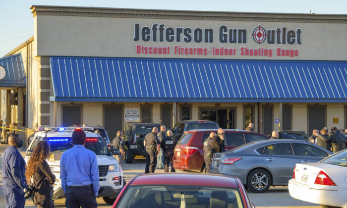 Bystanders react at the scene of a multiple fatality shooting at the Jefferson Gun Outlet in Metairie, La., on Feb. 20, 2021. (AP Photo/Matthew Hinton)