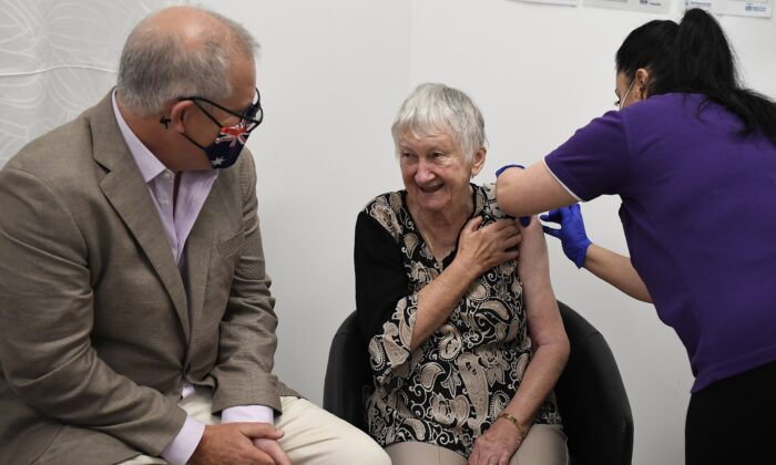 Australian Prime Minister Scott Morrison joins Aged care resident Jane Malysiak (left) as she receives the first Codid-19 vaccine in Australia during a visit to Castle Hill Medical Centre to preview the COVID-19 vaccination program on Feb. 21, 2021. (AAP Image/Joel Carrett)
