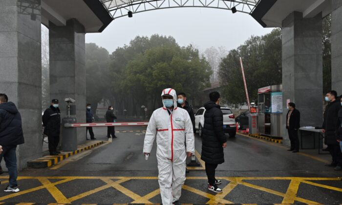 A guard wearing a protective gear at the entrance of the Hubei Provincial Center for Disease Control and Prevention as members of the World Health Organization team investigating the origins of COVID-19 visit Wuhan on Feb. 1, 2021. (Photo by HECTOR RETAMAL / AFP) (Photo by HECTOR RETAMAL/AFP via Getty Images)