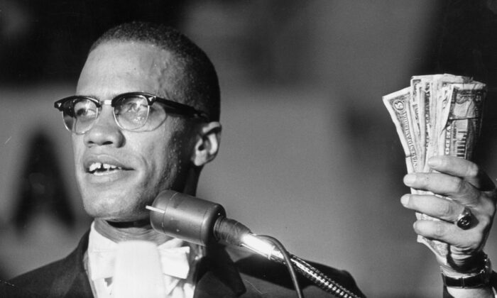 Headshot of American political activist Malcolm X (1925 - 1965) holding a fist full of U.S. currency during a speech at Urline Arena, Washington, in August 1963. (Richard Saunders/Hulton Archive/Getty Images)