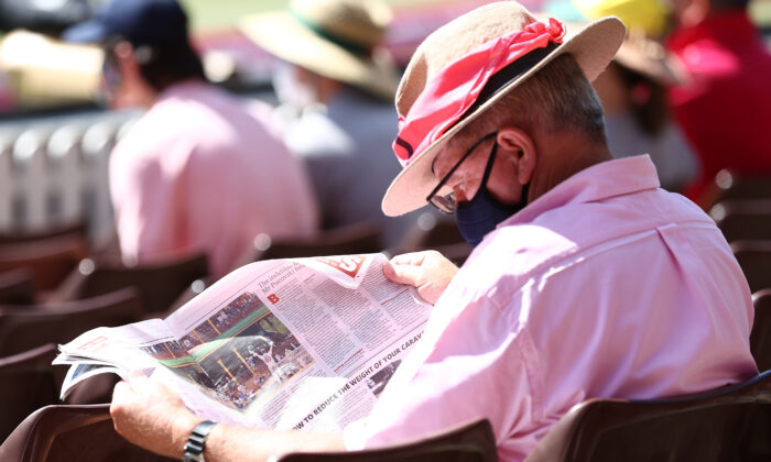 A spectator looks at a newspaper photograph  of Steve Smith of Australia on Jane McGrath Day during day three of the 3rd Test match in the series between Australia and India at Sydney Cricket Ground in Sydney, Australia on Jan. 9, 2021. (Ryan Pierse/Getty Images)