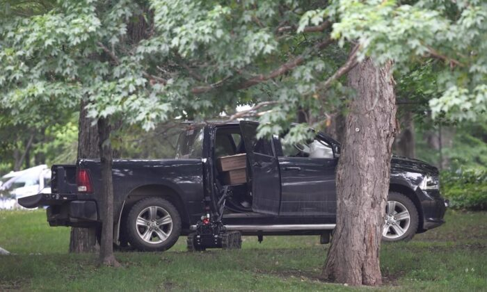 A police robot approaches a pickup truck inside the grounds of Rideau Hall in Ottawa on Thursday, July 2, 2020. (Adrian Wyld/The Canadian Press)