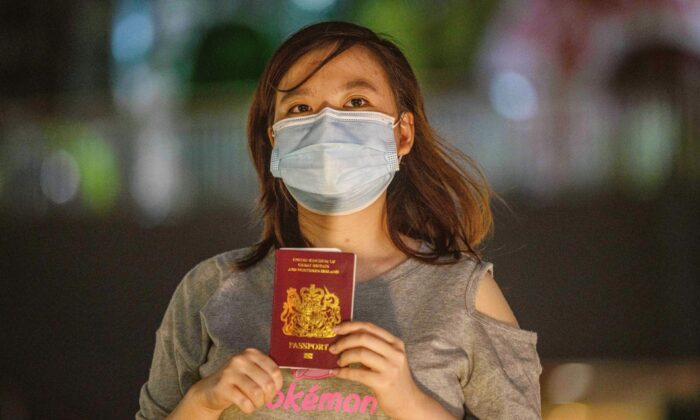 Recent graduate Asuka Law, 23, poses with her British National (Overseas), or BN(O), passport in her favourite part of the city and the place she would miss the most if she leaves, near a shopping mall, in Kwai Chung, Hong Kong, on June 3, 2020. (Anthony Wallace/AFP via Getty Images)