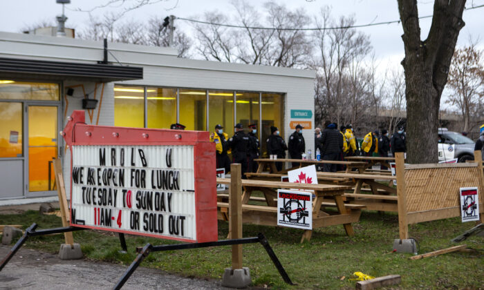 Police gather outside Adamson BBQ following the arrest of owner Adam Skelly in Etobicoke, Canada, on Nov 26, 2020. (Chris Young/The Canadian Press)