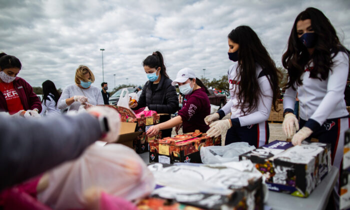 Texans Cheerleaders and other volunteers pack food to distribute to hundreds of people picking up supplies from their cars after frigid temperatures left the Houston area depleted of resources in Houston on Feb. 21, 2021. (Marie D. De Jesús/Houston Chronicle via AP)