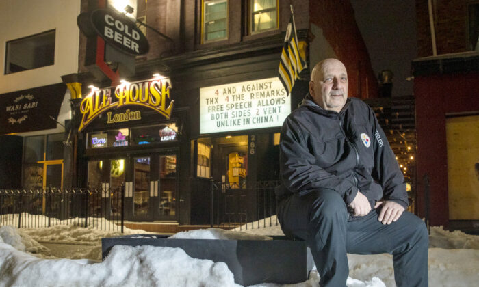 Alex Petro sits outside his bar, Ale House, with his latest sign in the background, in London, Ont., on Feb. 22, 2021. (Jason Ransom)