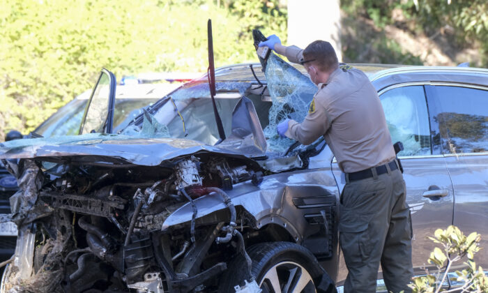 A law enforcement officer looks over a damaged vehicle following a rollover accident involving golfer Tiger Woods, in the Rancho Palos Verdes suburb of Los Angeles, Calif., on Feb. 23, 2021. (Ringo H.W. Chiu/AP Photo)