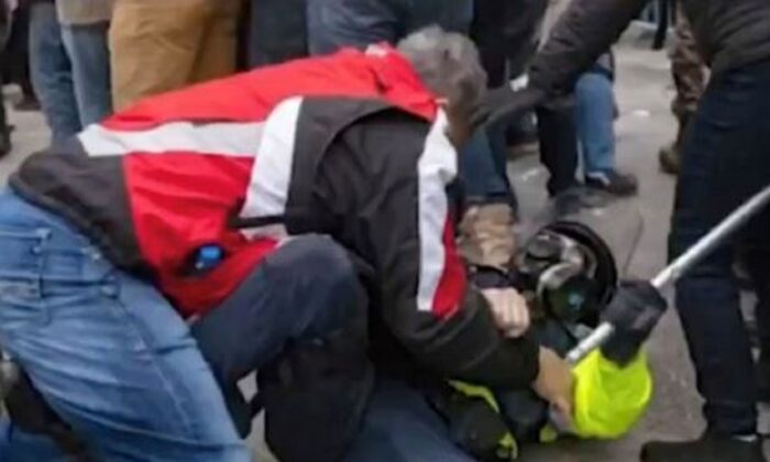 A man identified as Thomas Webster (L) pins a police officer on the ground in Washington on Jan. 6, 2021. (DOJ)