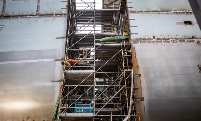 Workers climb scaffolding on a Joint Support Ship being built for the Royal Canadian Navy at Seaspan Shipyards in North Vancouver, B.C., on Oct. 9, 2020. (Darryl Dyck/The Canadian Press)