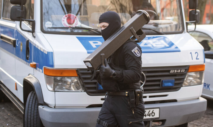 A police walks in front of a car during raids against an Islamist network at the Maerkische Viertel neighborhood in Berlin, on Feb. 25, 2021. (Christophe Gateau/DAP via AP)