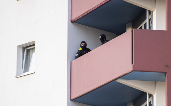 Police officers stand on a balcony of an apartment building during raids against an Islamist network at the Maerkische Viertel neighborhood in Berlin