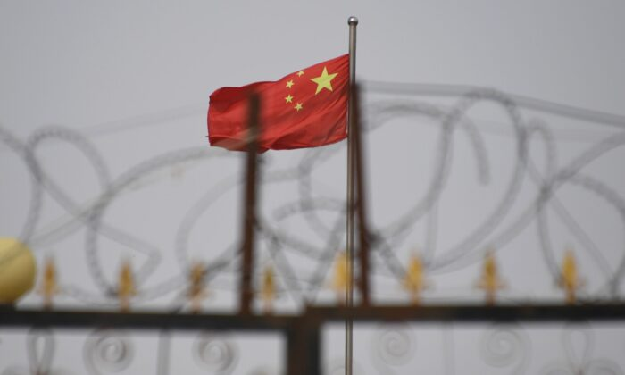 The Chinese Communist Party flag behind razor wire at a housing compound in Yangisar, south of Kashgar, in China's western Xinjiang region, on June 4, 2019. (Greg Baker/AFP) (Greg Baker/AFP via Getty Images)