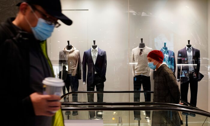 People wearing facemasks pass by a men's clothing store at The Shops at Columbus Circle in New York, on Feb. 15, 2021. (Timothy A. Clary/AFP via Getty Images)