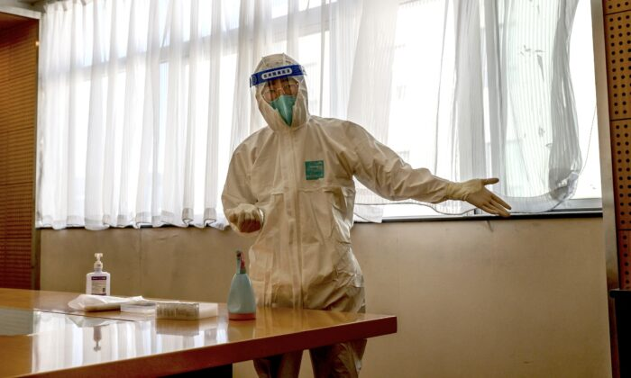 A health worker wears a protective suit as he gestures to a man to sit down at a hotel in Beijing, China, before a COVID-19 nucleic acid test on Oct. 22, 2020. (Kevin Frayer/Getty Images)