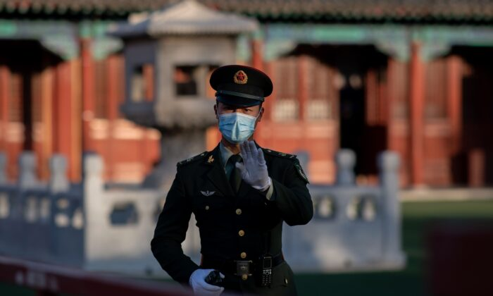 A soldier wearing a mask gestures outside the Forbidden City in Beijing on Oct. 22, 2020. (Nicolas Asfouri/AFP via Getty Images)