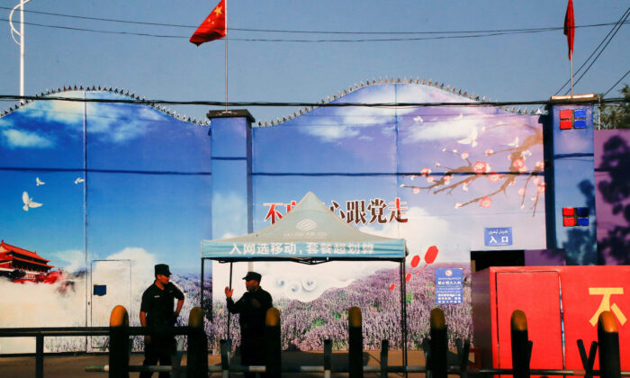 Security guards stand at the gates of what is officially known as a vocational skills education centre in Huocheng County in Xinjiang Uighur Autonomous Region on Sep. 3 2018. (Thomas Peter/ Reuters)