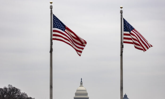 The U.S. Capitol building is seen past American flags at the base of the Washington Monument in Washington on Feb. 15, 2021. (Samuel Corum/Getty Images)