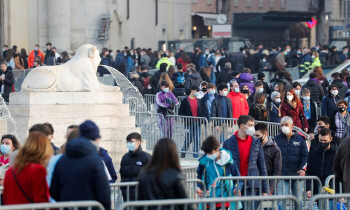 Barriers to control the pedestrian traffic are seen as people walk at Piazza del Popolo, in Rome, Italy, Feb. 27, 2021. (Remo Casilli/Reuters)