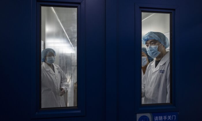 Workers wait to open the secure door in the packaging area of Sinopharm CNBG's inactivated SARS-CoV-2 vaccine for COVID-19 during a media tour organized by the State Council Information Office in Beijing on Feb. 26, 2021. (Kevin Frayer/Getty Images)