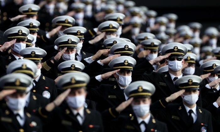 Midshipmen wear masks as they stand and salute for the U.S. National Anthem before the Navy Midshipmen play against the Houston Cougars at Navy-Marine Corps Memorial Stadium in Annapolis, Md., on Oct. 24, 2020. (Patrick Smith/Getty Images)
