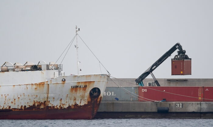 """A crane moves a container next to livestock ship """"Karim Allah,"""" that carries nearly a thousand Spanish cattle stranded on ship with suspected bluetongue disease, at Escombreras port, in Cartagena, Spain, Feb. 27, 2021. (Juan Medina/Reuters)"""