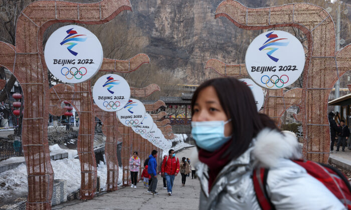 People wear protective masks as they walk in front of logos for the 2022 Beijing Winter Olympics at Yanqing Ice Festival in Beijing, on Feb. 26, 2021. (Lintao Zhang/Getty Images)