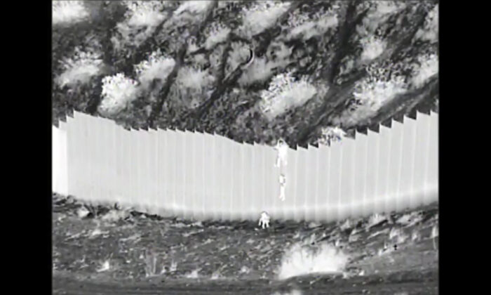 Video screenshot shows a human smuggler dropping a child over the U.S. border wall in the desert in New Mexico. (U.S. Customs and Border Protection)