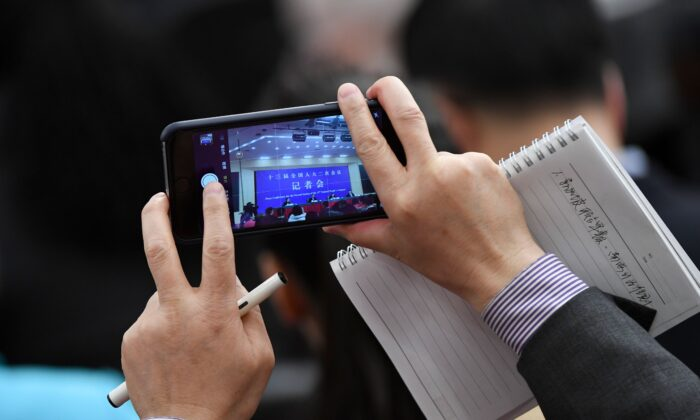 A journalist takes a picture during a National People's Congress press conference in Beijing, on March 8, 2019. (Wang Zhao/AFP via Getty Images)