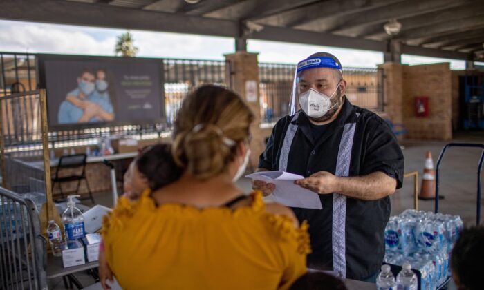 Asylum-seekers register for rapid COVID-19 tests in an isolation area at a bus station in Brownsville, Texas, on Feb. 26, 2021. (John Moore/Getty Images)