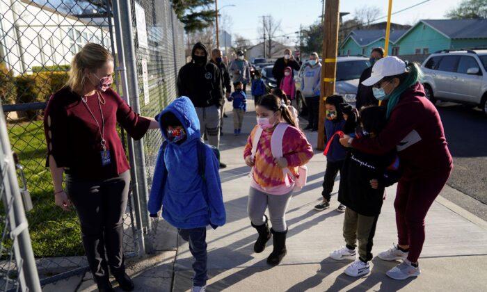 Assistant Principal Janette Van Gelderen (L) welcomes students at Newhall Elementary in Santa Clarita, Calif., on Feb 15, 2021. (Marcio Jose Sanchez/AP Photo)