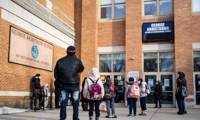 Parents and children line up outside George B. Armstrong International Studies Elementary School in Chicago, Ill., on March 1, 2021. (Ashlee Rezin Garcia/Chicago Sun-Times via AP)